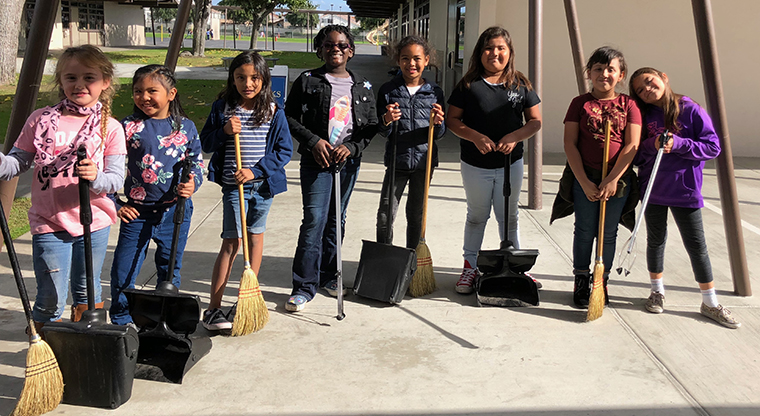 students with brooms and dustpans